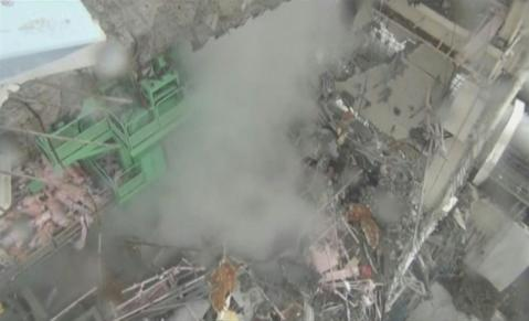 An overview shows smoke rising from the interior of reactor No. 4 at the Fukushima Daiichi nuclear power plant complex in this still image taken from a March 24, 2011 handout video released on April 1, 2011.